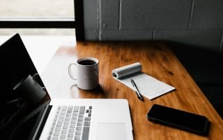 A Laptop, Mug of Coffee, Mobile and a Notepad with Pen Are Placed on a Table.
